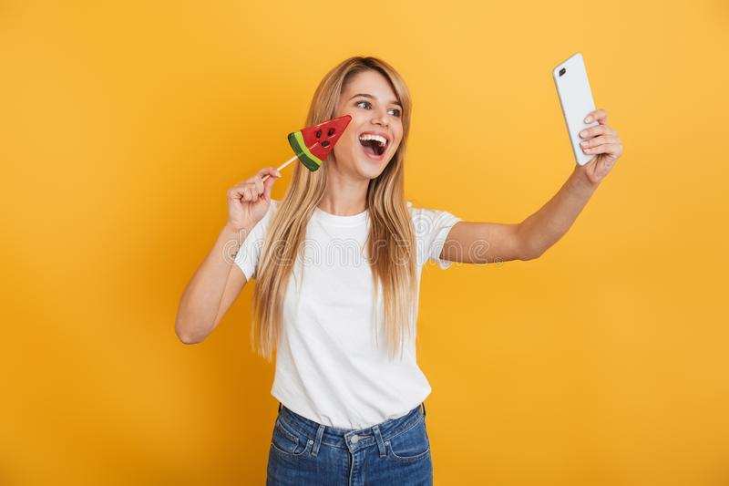 Happy pleased positive young blonde woman jumping isolated over yellow wall background dressed in white casual t-shirt holding. Image of happy pleased positive royalty free stock photography