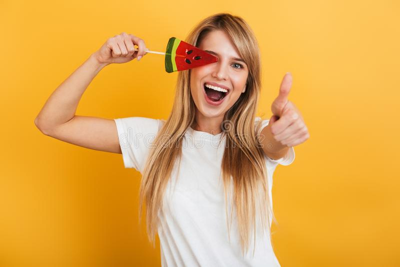 Happy pleased positive young blonde woman jumping isolated over yellow wall background dressed in white casual t-shirt holding. Image of smiling young blonde royalty free stock images