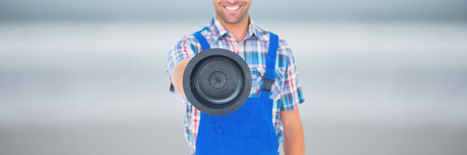 Happy plumber man holding a plunger. Digital composite of Happy plumber man holding a plunger royalty free stock photo