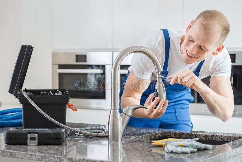 Happy plumber repairing kitchen`s faucet stock images