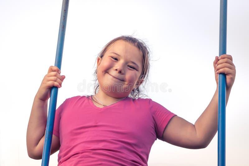 Happy plump child girl fun swinging sky happy carefree childhood stock photo