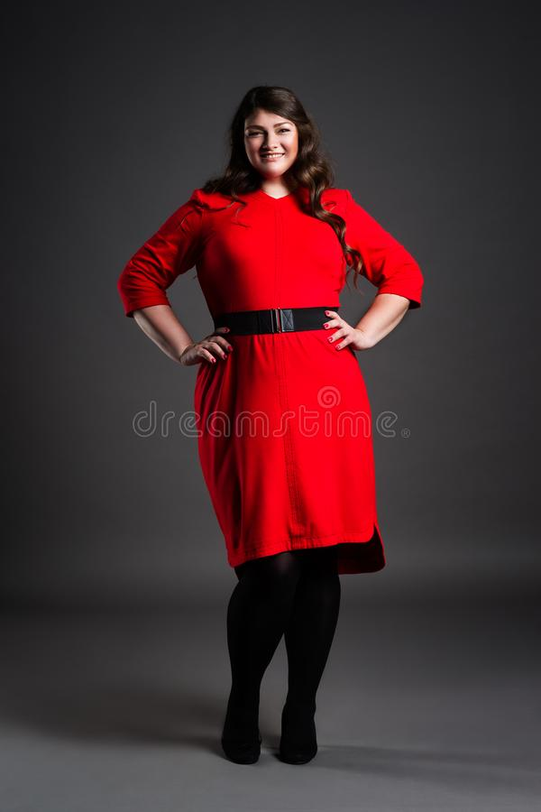 Happy plus size fashion model in red dress, fat woman on gray background, overweight female body. Happy plus size fashion model in red dress, fat woman on gray stock image