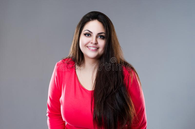 Happy plus size fashion model in red dress, sexy fat woman on gray background, body positive concept royalty free stock photos