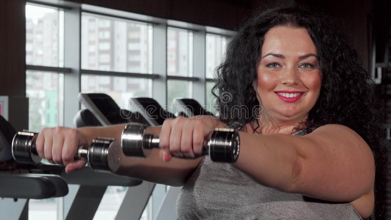 Happy plus size sportswoman lifting dumbbells at the gym stock photography