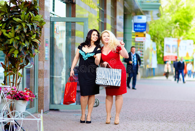 Happy plus size women shopping. Two happy plus size women shopping stock photos