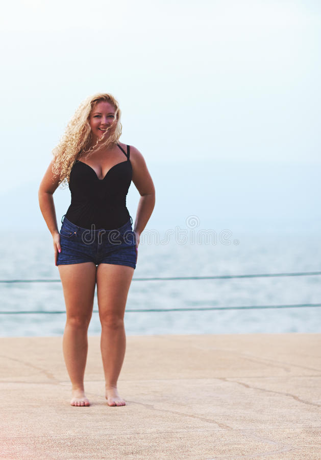 Happy plus size young woman near the sea royalty free stock image