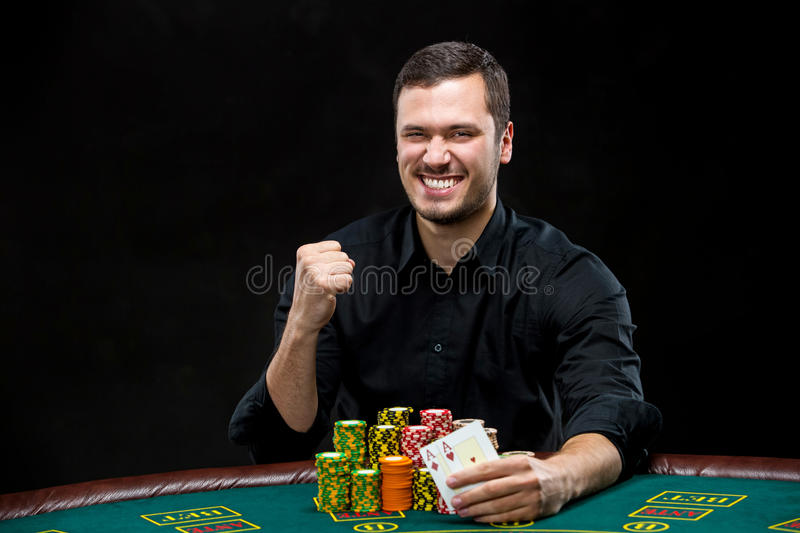 Happy poker player winning and holding a pair of aces. Concept of winning or having the upper hand royalty free stock photo