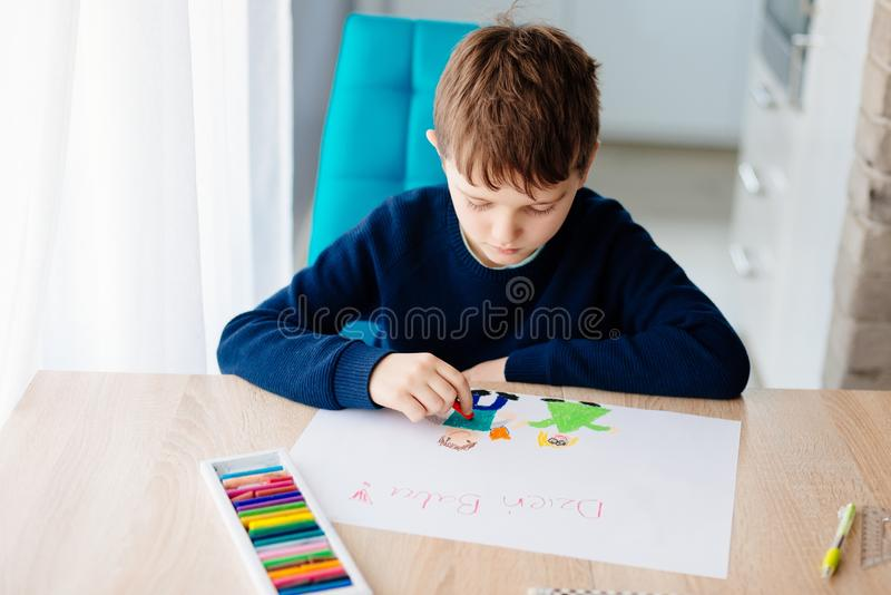 Happy Polish child drawing a greeting card for his grandma. royalty free stock image