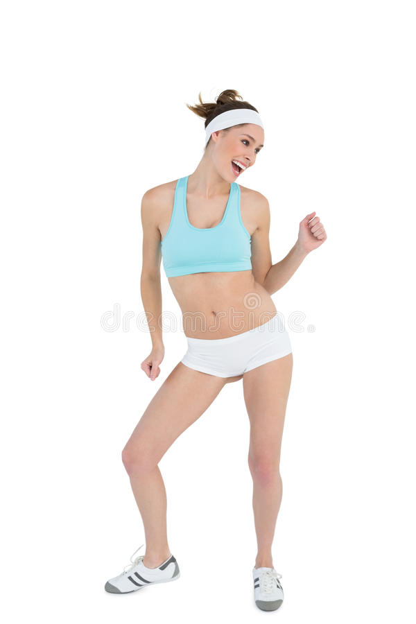 Happy ponytailed woman dancing wearing sportswear stock images