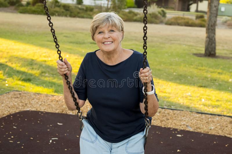 Happy portrait of American senior mature beautiful woman on her 70s sitting on park swing outdoors relaxed smiling and having fun. In healthy aging and royalty free stock image