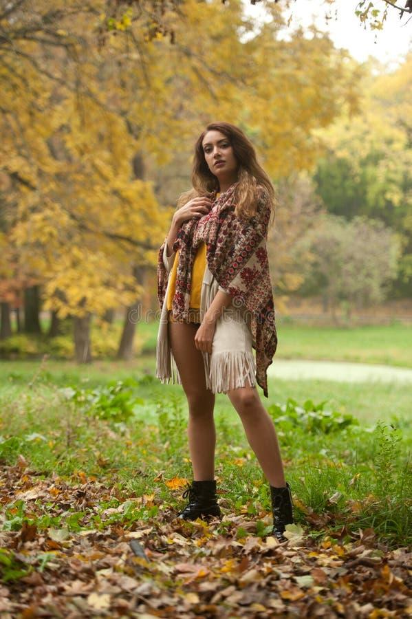 Happy Portrait d'une belle jeune femme du Caucase avec foulard, jambes longues et pull-over jaune dans le parc d'automne images stock