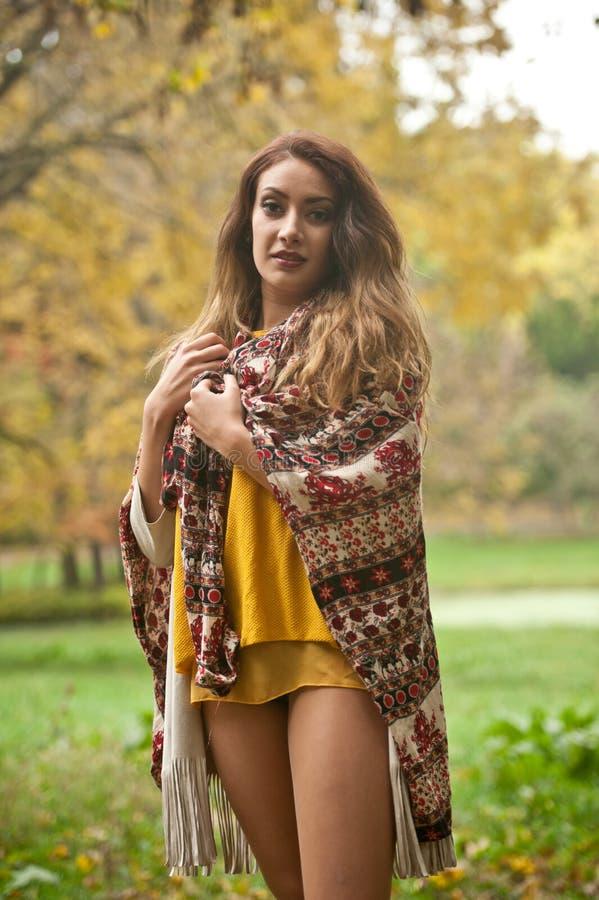 Happy Portrait d'une belle jeune femme du Caucase avec foulard, jambes longues et pull-over jaune dans le parc d'automne photo stock
