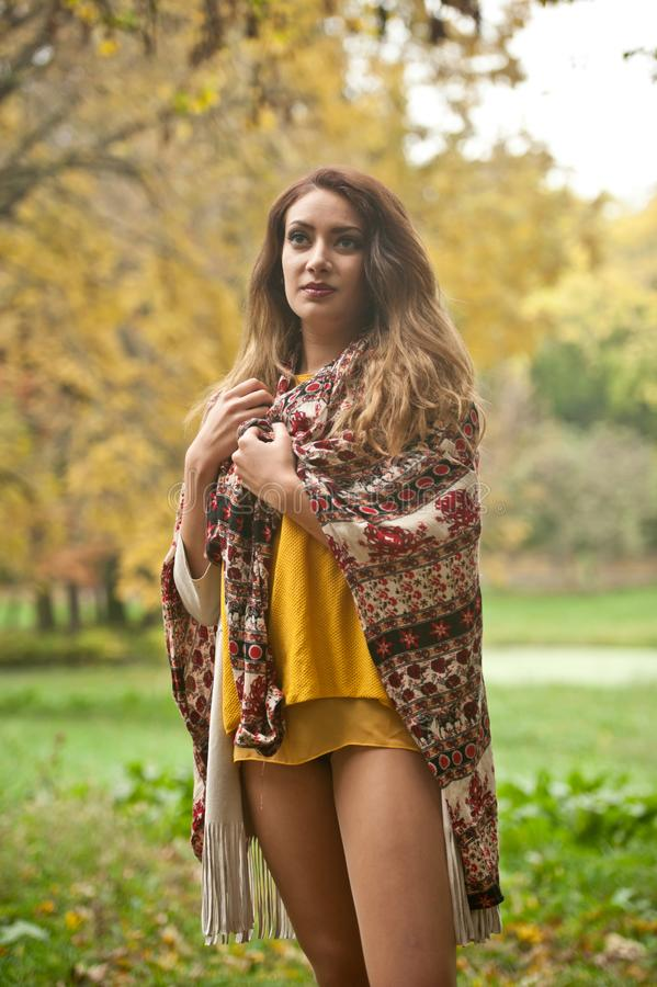 Happy Portrait d'une belle jeune femme du Caucase avec foulard, jambes longues et pull-over jaune dans le parc d'automne photos stock