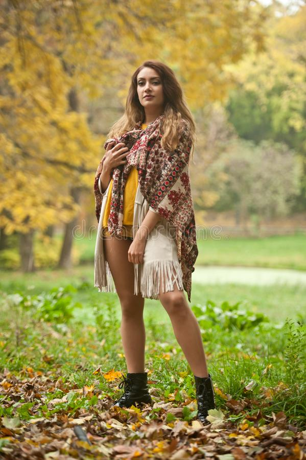 Happy Portrait fashion of a beautiful young Caucasian woman with a scarf,long legs  and yellow pullover in autumn park royalty free stock images