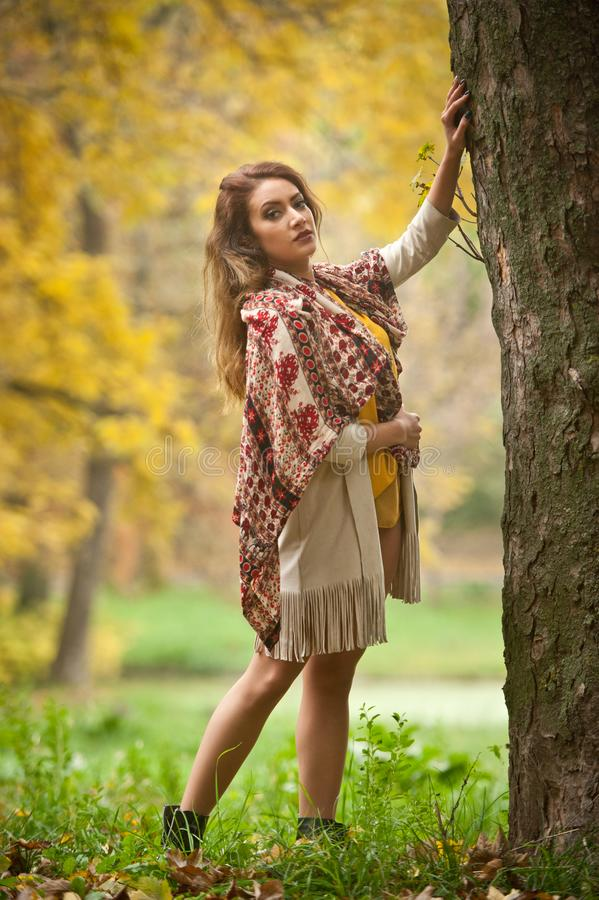 Happy Portrait fashion of a beautiful young Caucasian woman with a scarf,long legs  and yellow pullover in autumn park stock photo
