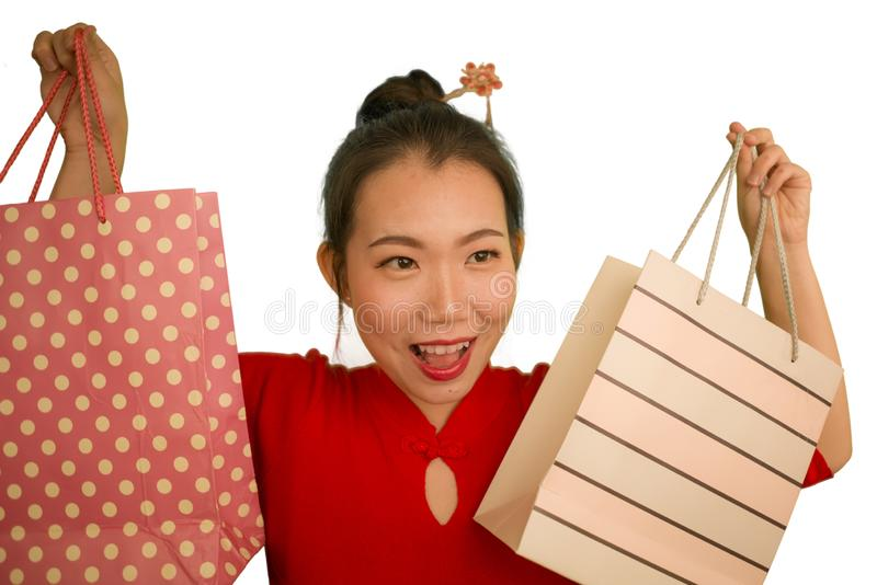 Happy portrait of young beautiful and excited Asian Japanese woman in red dress smiling excited holding shopping bags cheerful royalty free stock images