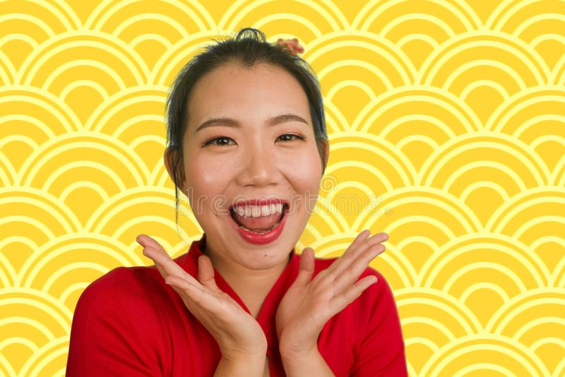 Happy portrait of young beautiful and sweet Asian Chinese woman in traditional bun hair style and red dress celebrating New Year royalty free stock photography