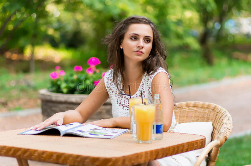 Happy, positive, beautiful, elegance girl sitting at cafe table outdoors. stock photo