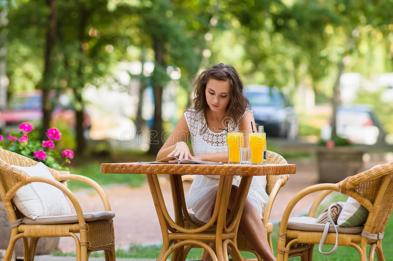 Happy, positive, beautiful, elegance girl sitting at cafe table outdoors. royalty free stock images