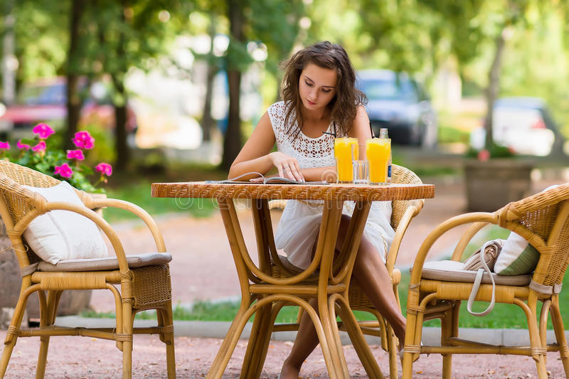 Happy, positive, beautiful, elegance girl sitting at cafe table outdoors. royalty free stock photography