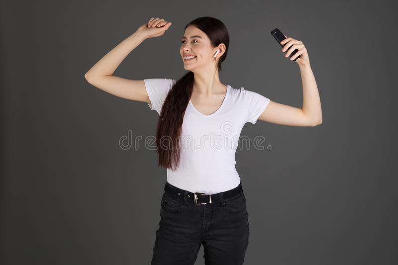 Happy positive brunette woman in white t-shirt and dark jeans stock photography