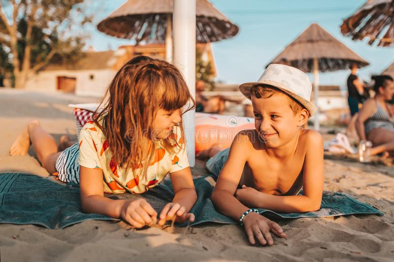 Happy positive children lying on a towel on the beach stock photo