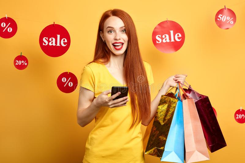 Happy positive girl texting message, sms to her friend royalty free stock images