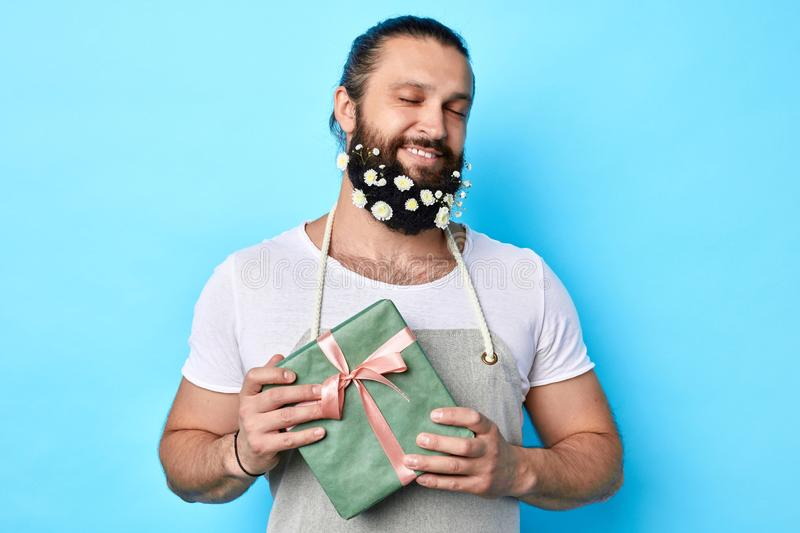 Happy positive handsome man with flowers in his beard holding gift box in hands royalty free stock photography