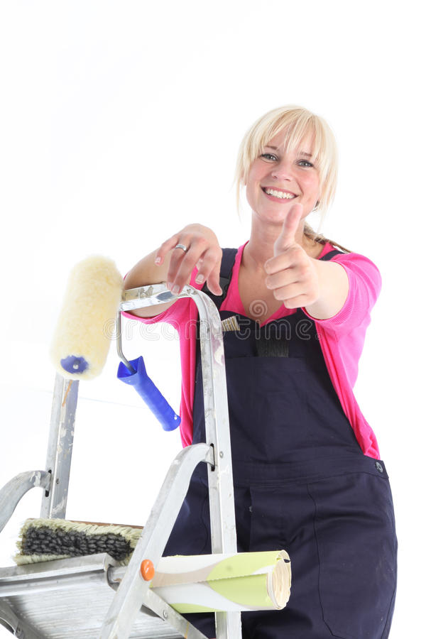 Happy positive housewife wallpapering. Looking down from the top of her ladder giving a thumbs up gesture stock photo