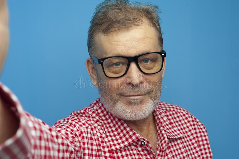 Happy positive man pensioner wearing red shirt and stylish eyeglasses. Portrait of Happy positive man pensioner wearing red shirt and stylish eyeglasses making stock photos