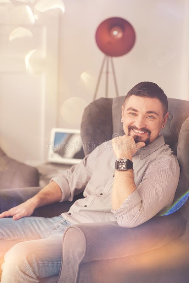 Happy positive man sitting in the armchair royalty free stock photos