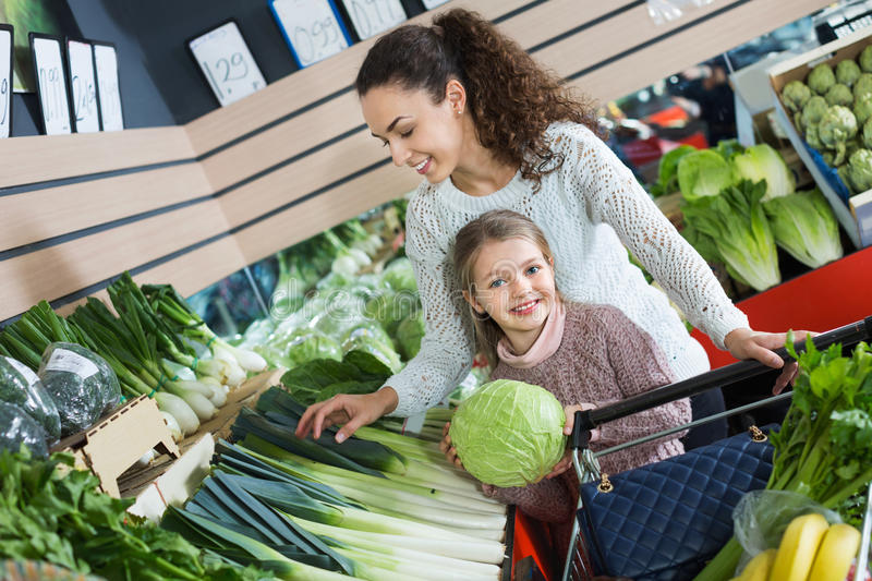 Happy positive mother with smiling small daughter. Buying fresh celery and cabbage royalty free stock photos