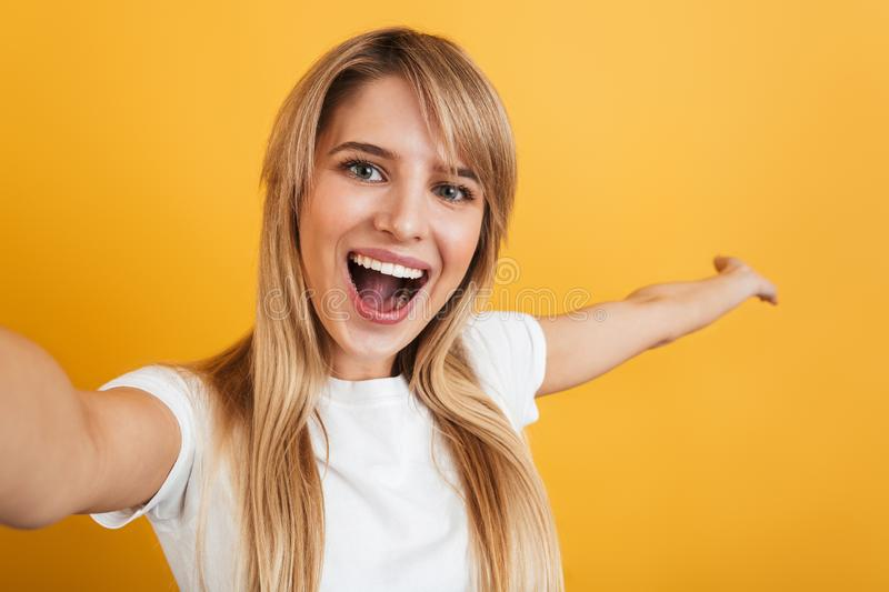 Happy positive pleased young blonde woman posing isolated over yellow wall background dressed in white casual t-shirt take selfie royalty free stock images