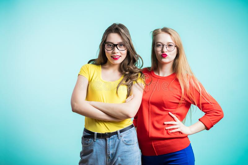 Happy positive two stylish girls hugging stand near the blue wall. Close up portrait funny joyful attarctive young women. royalty free stock photos