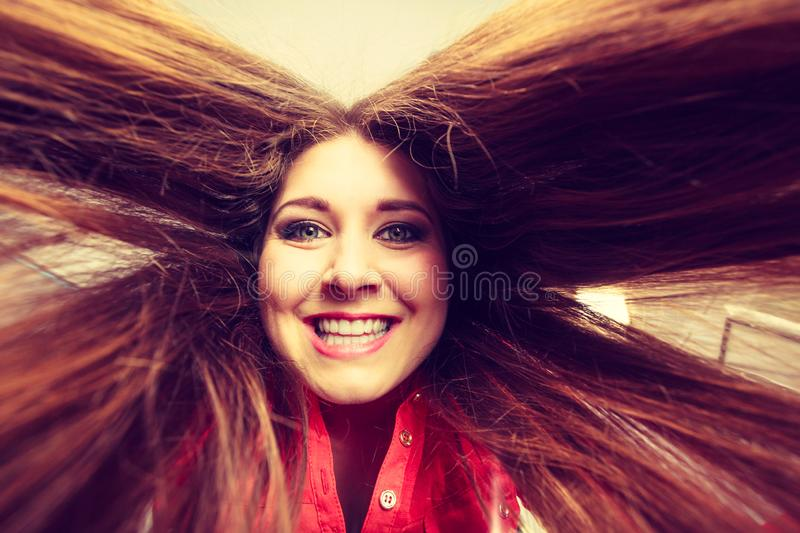 Happy positive woman with long brown hair. Presenting her healthy hairdo. Haircare concept royalty free stock images