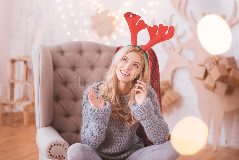 Happy positive woman putting a smartphone to her ear. Long distance communication. Happy cute positive woman wearing toy reindeer horns and putting a smartphone royalty free stock photos