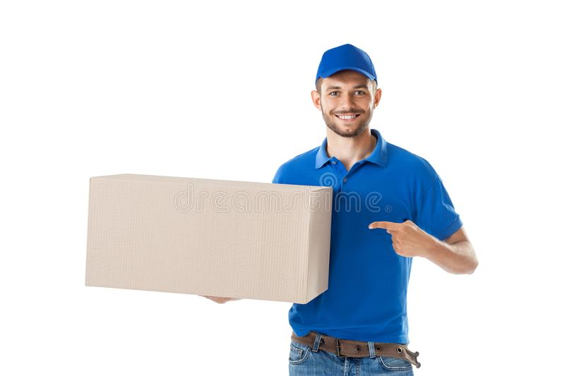 Happy postman shows on big box isolated on white background. Deliverer with large cardboard parcel in hands royalty free stock image