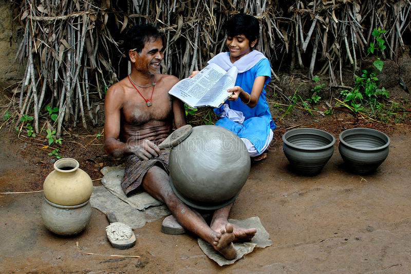 Happy Potter. A potter talk to her daughter while he is working in the remote village of West Bengal-India