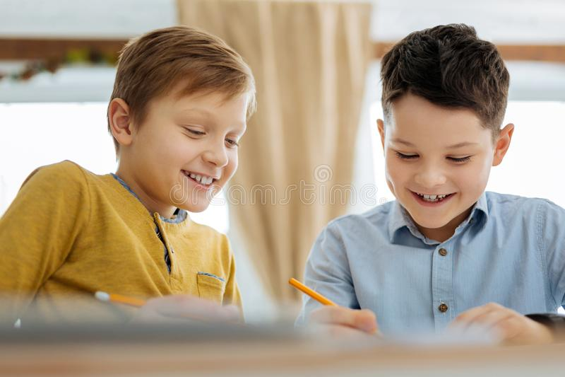 Happy pre-teen boys drawing together royalty free stock image