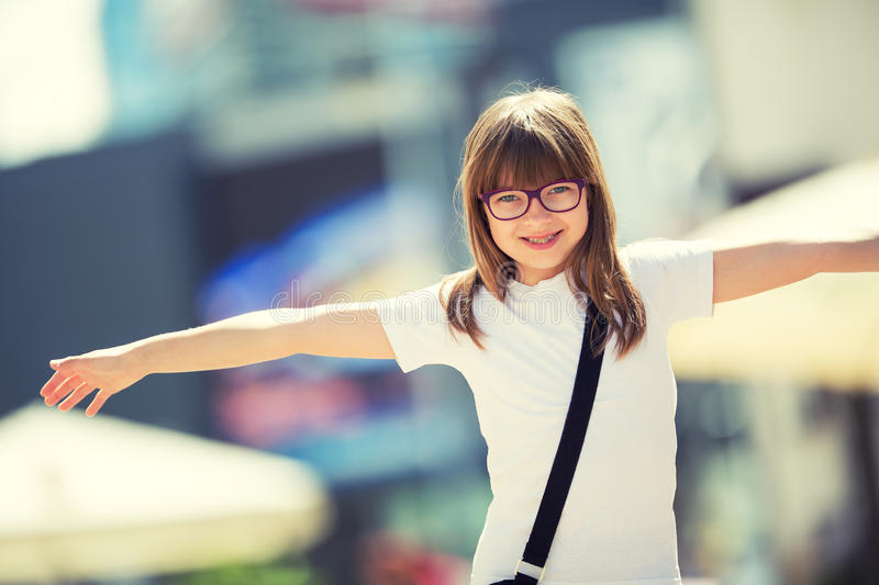Happy pre-teen young girl. Cute little girl in the city on a sunny day. Portrait young girl. Toned image royalty free stock images