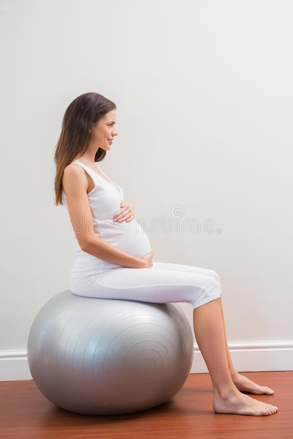 Happy pregnancy sitting on exercice ball. On room stock photography