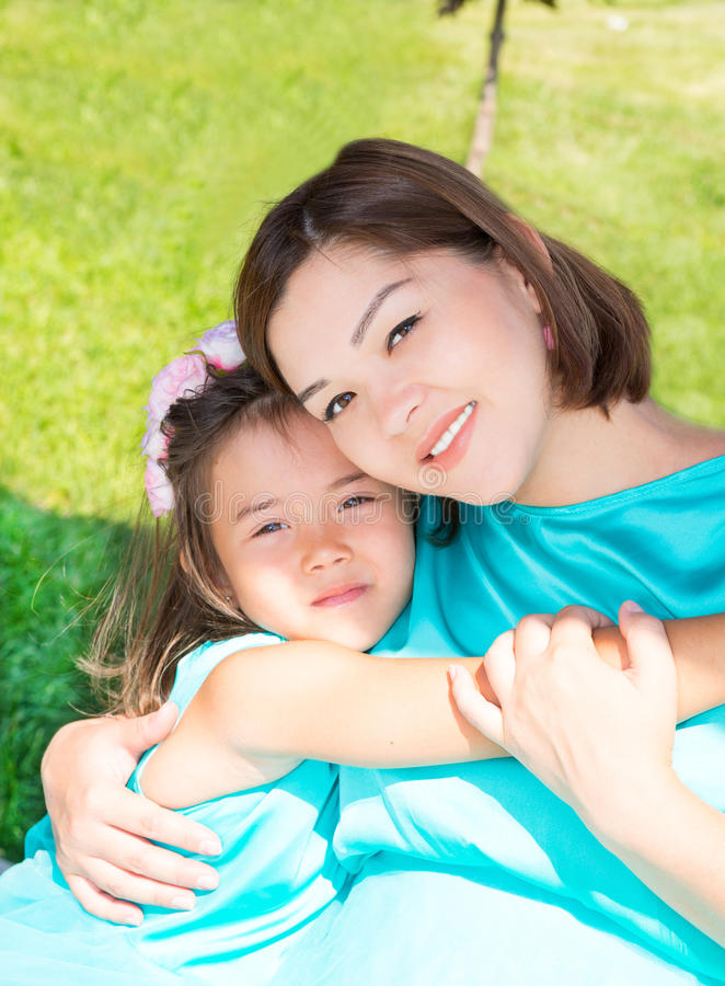 Happy pregnant asian mom and child girl hugging. The concept of childhood and family. Beautiful Mother and her baby outdoor stock images