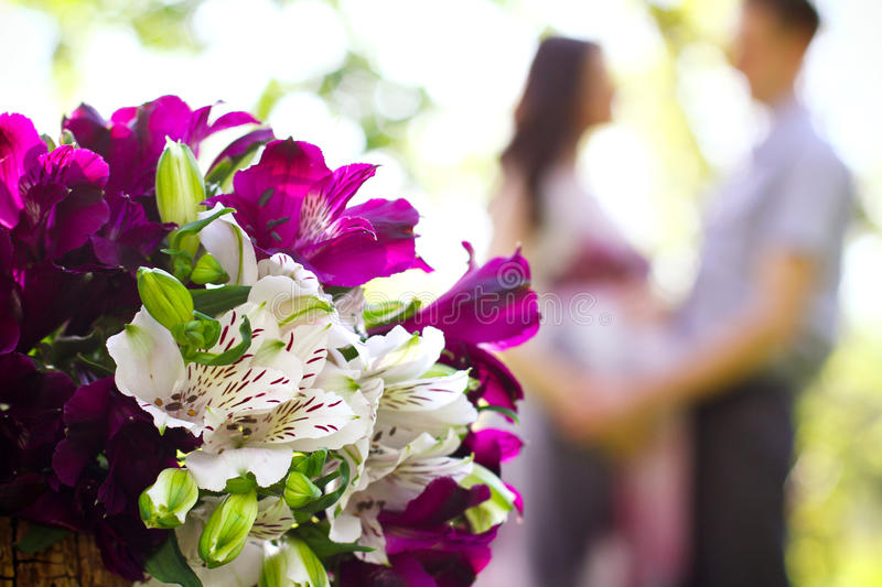 Happy pregnant couple and bouquet of flowers in the foreground royalty free stock photography