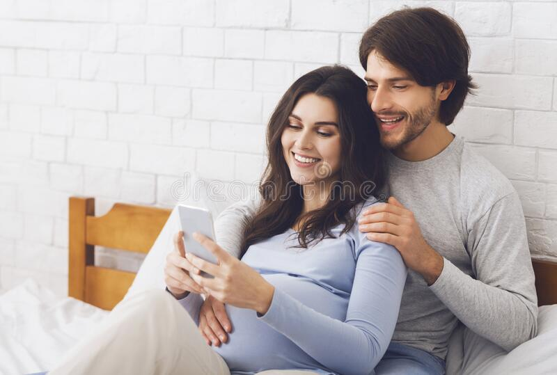 Happy expecting couple posing for selfie, cuddling in bed at home royalty free stock photo