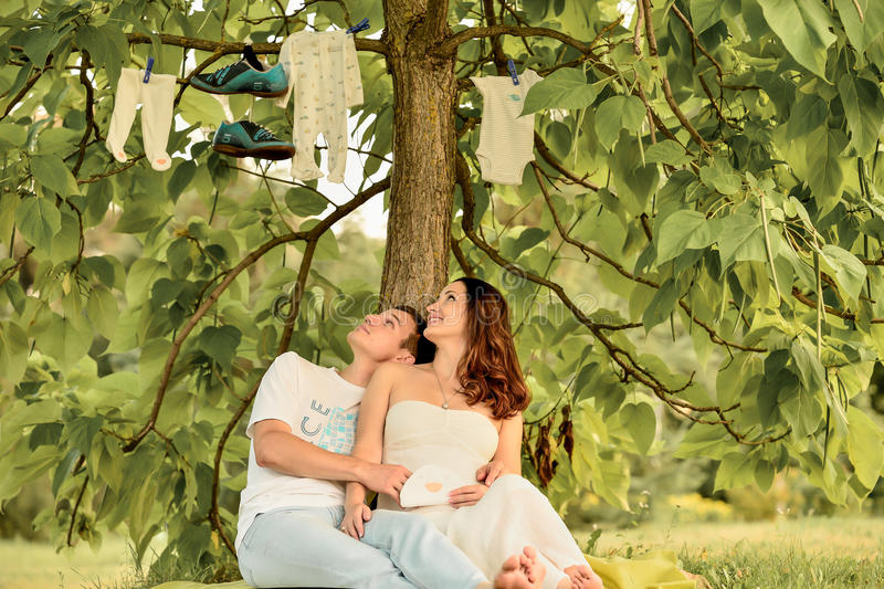 Happy pregnant couple sitting on the banch in park stock photos