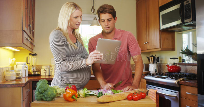 Happy pregnant couple working together in the kitchen. At home royalty free stock images