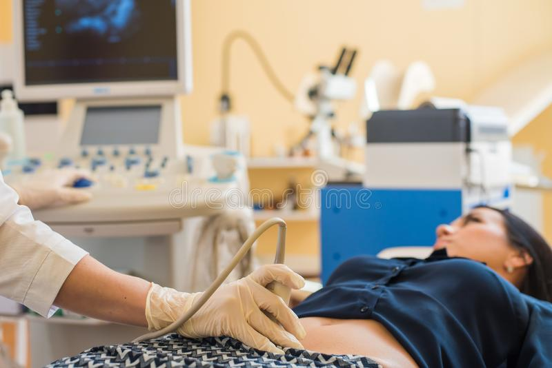 Ultrasound test. Pregnancy. Gynecologist checking fetal life with scanner. Exam. Happy pregnant female visiting women`s doctor in the maternity center, doing royalty free stock photos