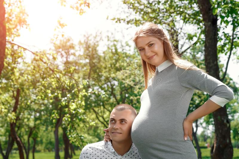Happy pregnant woman, family couple in the park, green floral background. man listens to the belly of a beautiful pregnant wife. Happy pregnant, married couple stock image
