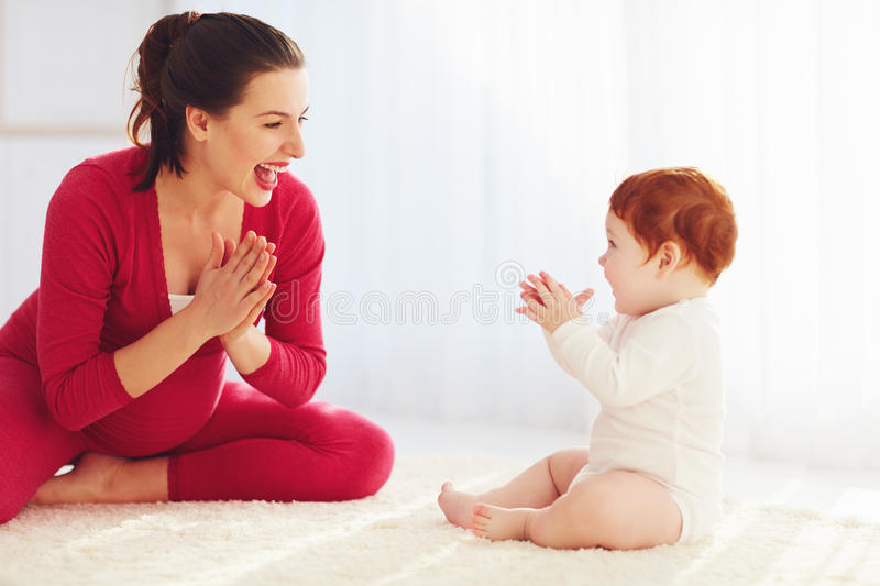 Happy pregnant mother and toddler baby playing games at home, clapping hands together stock photos