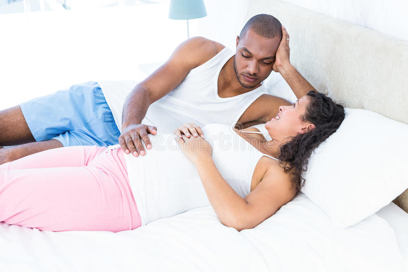 Happy pregnant wife relaxing with husband on bed royalty free stock photography